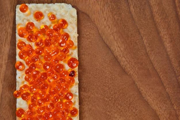 Cracker met rode kaviaar op hout.