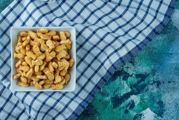 Cracker vis in kom op theedoek op blauw.