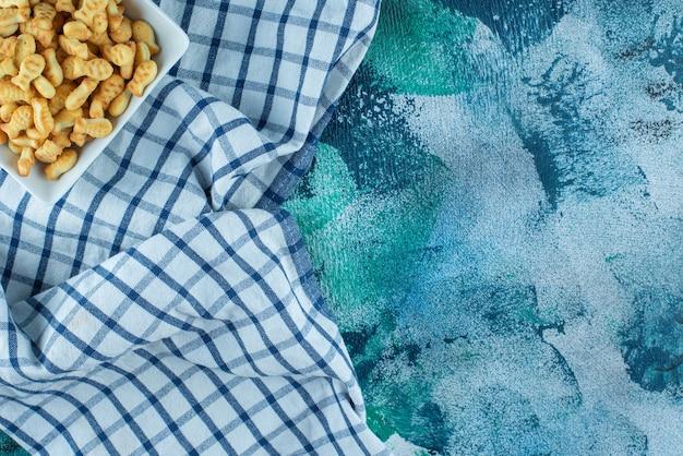 Cracker vis in kom op theedoek, op de blauwe tafel.