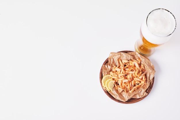 Crackers en chips met een glas bier op wit.