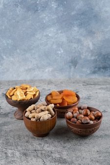 Crackers, gedroogde abrikozen, hazelnoten en pinda's in houten kommen.
