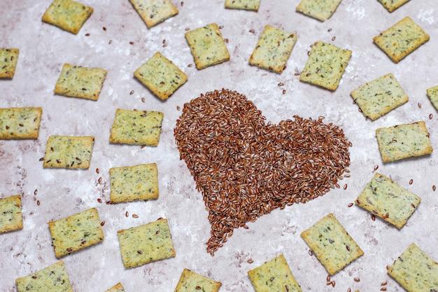 Crackers in de vorm van hart van linnen zaden met olijfolie, linnen zaden en greens, bovenaanzicht