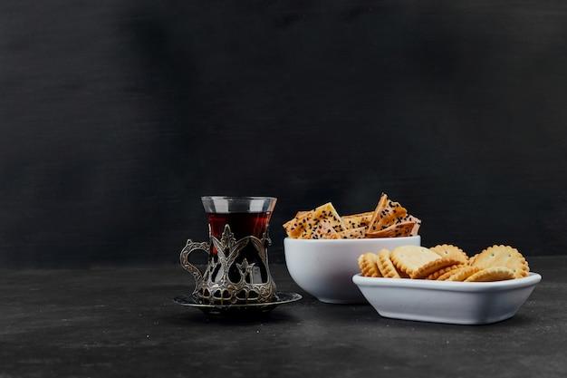 Crackers in witte keramische schoteltjes met een glas thee op zwart.