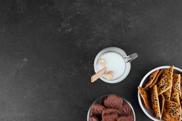Crackers met een glas melk op zwart, bovenaanzicht.