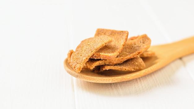 Crackers met kruiden in een houten lepel op een witte houten tafel.