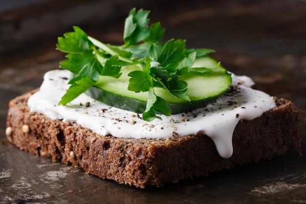 Crackers met kwark, radijs, komkommer versierd met tuinkerssalade en verse kruiden