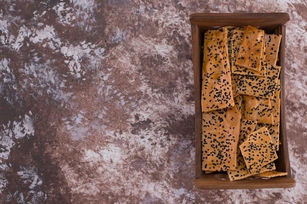 Crackers met zwarte komijn erop in houten bakje aan de rechterkant.