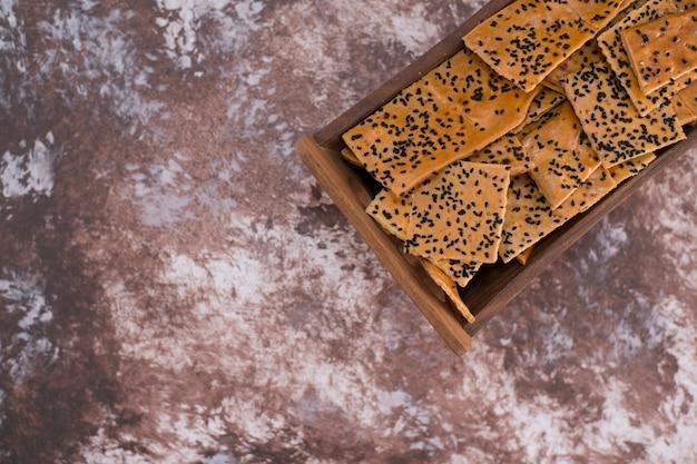 Crackers met zwarte komijn erop in houten bakje in de bovenhoek