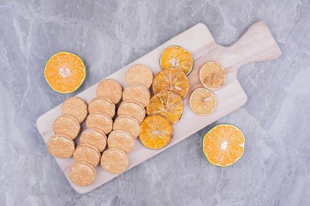 Crackers op een houten schotel met stukjes sinaasappel eromheen