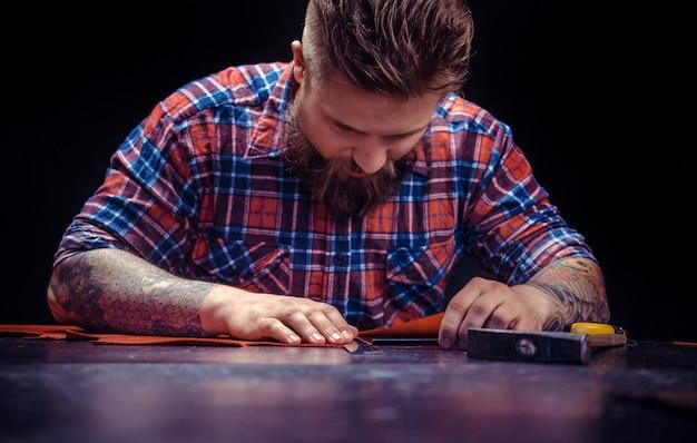 Craftsman vervaardigt een nieuw product gemaakt van leer