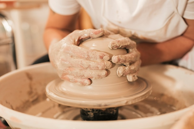 Craftswoman die aardewerk maakt dat aan de wiel vormende klei werkt