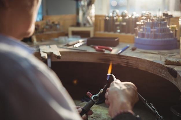 Craftswoman die toorts in workshop gebruiken