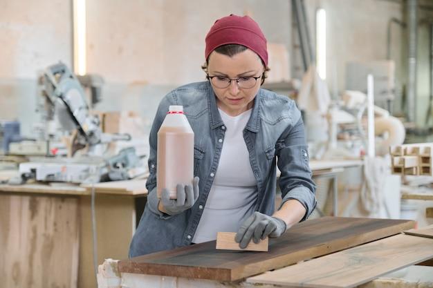 Craftswoman op middelbare leeftijd die in houtbewerkingsworkshop werken.