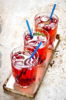 Cranberry-cocktail. drie bessencocktails met ijs en muntblaadjes op de oude rustieke achtergrond.