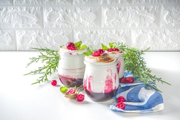 Cranberry gelaagd dessertontbijt in kleine potten voor kerstochtend. zelfgemaakt gebakken cranberry-meringue-dessert, met verse veenbessen en munt