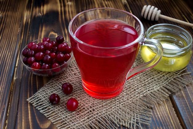 Cranberry-mors en honing op de rustieke houten achtergrond