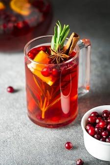 Cranberrythee, kaneel, sinaasappel, rozemarijn, steranijs en honing in een glazen mok op een grijze achtergrond