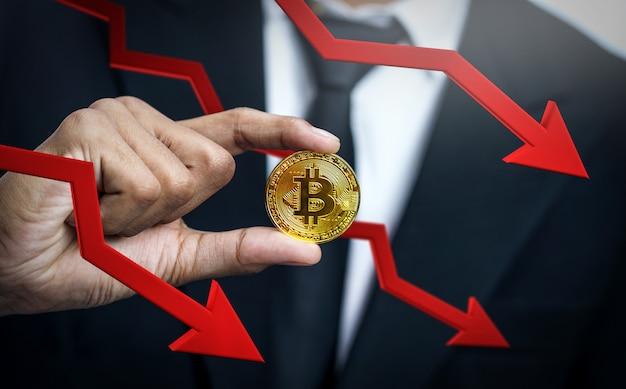 Crashing price van bitcoin. zakenman holding bitcoin met rode 3d pijl-omlaag