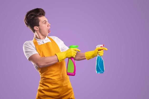 Crazy man in schort en handschoenen schreeuwen en wasmiddelen uit flessen spuiten tijdens de schoonmaak routine op violette achtergrond
