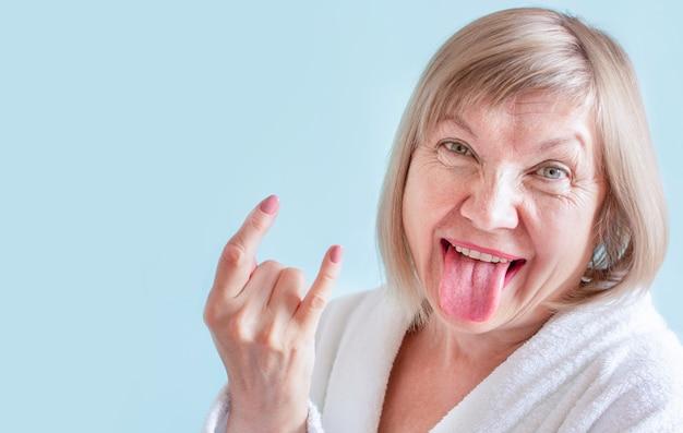 Crazy senior vrouw anti leeftijd concept funky tong uit. ouderdom in vreugde, over anciënniteit, schattige grootmoeder, gezondheidszorg, cosmetologie, gepensioneerde en volwassen mensen, nieuwe senior