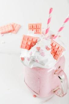 Crazy shake, romantische milkshake voor valentijnsdag met aardbeien, witte chocolade en suiker snoep harten, op wit, copyspace