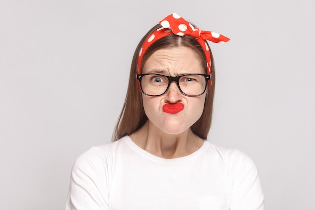 Crazy vroeg zich af grappig portret van mooie emotionele jonge vrouw in wit t-shirt met sproeten, zwarte bril, rode lippen en hoofdband. indoor studio opname, geïsoleerd op lichtgrijze achtergrond.
