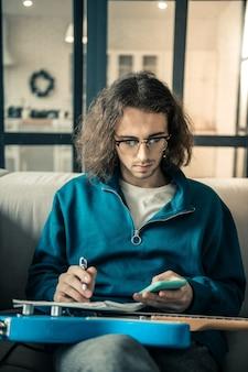 Creatie proces. rustige langharige muzikant met een heldere bril terwijl hij de smartphone controleert en een nieuwe compositie maakt