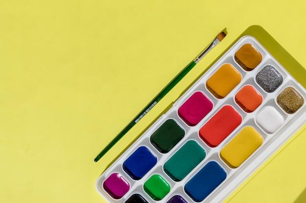Creatie, tekenen en vrijheid concept - artistieke apparatuur: penselen, aquarellen schilderijen op gele achtergrond. verf apparatuur: penselen, tekenles. kopieer ruimte