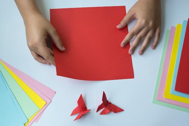Creatie van origami een vlinder. de handen van kinderen doen origami een vlinder.