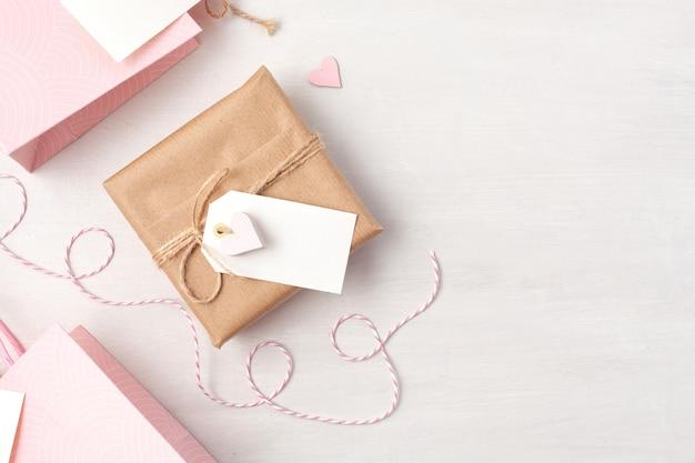 Creatief beeld van giftzak en doos met lege markering, hart en kerstmisdecoratie in roze pastelkleuren.