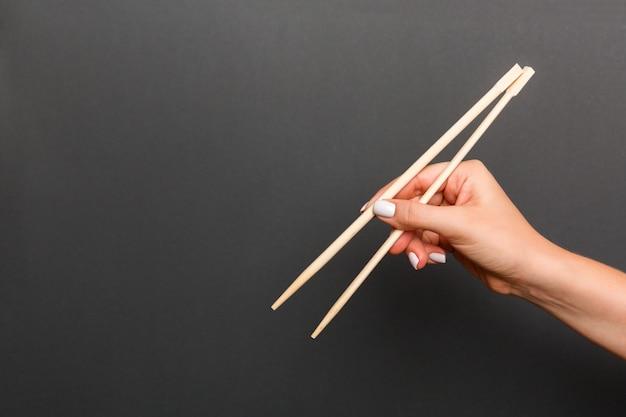 Creatief beeld van houten eetstokjes in vrouwelijke hand op zwarte. japans en chinees eten met copyspace
