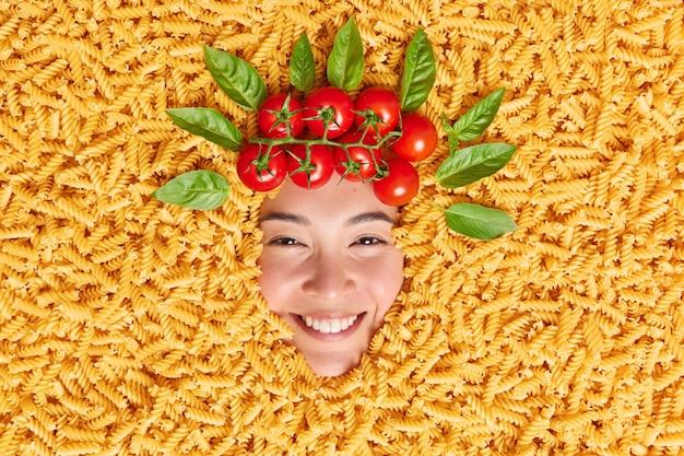 Creatief beeld van menselijk gezicht omringd door macaroni verse rode tomaten en basilicumbladeren alsof haar. Premium Foto