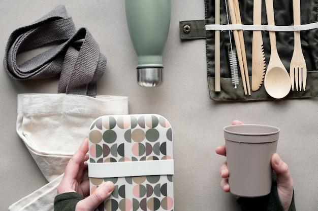 Creatief bovenaanzicht, lunchpakket zonder afvalpakket, afhaalmaaltijdenlunchdoos met bamboe bestek, herbruikbare doos, katoenen tas en hand met coffee-to-go beker. eco-vriendelijk wonen, plat op ambachtelijk papier.