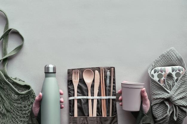 Creatief bovenaanzicht, lunchpakket zonder afvalpakket, afhaalmaaltijdenlunchdoos met bamboebestek, herbruikbare doos, katoenen tas en hand met coffee-to-go-kop hierboven op pakpapier. duurzame levensstijl.