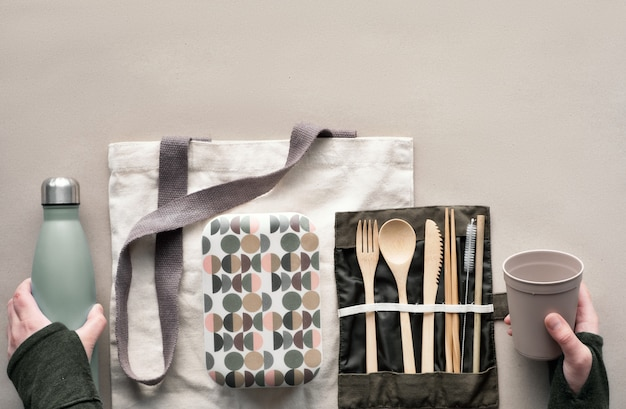 Creatief bovenaanzicht, lunchpakket zonder afvalpakket, meeneemlunchdoos met bamboe bestek, herbruikbare doos, katoenen tas en hand met koffie-to-go kopje hierboven op ambachtelijk papier. duurzame levensstijl.