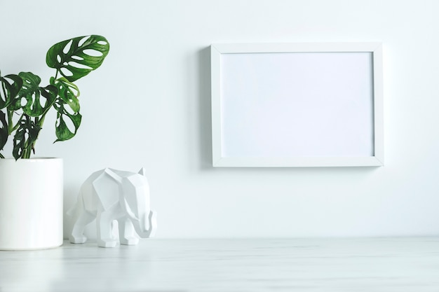 Creatief bureau in scandinavische stijl met witte mock-up posterframe, witte figuur van olifant en plant in klassieke pot. wit minimalistisch concept.