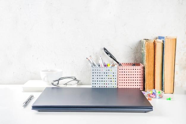Creatief bureau met benodigdheden en koffiekopje. witte kantoor tafel met laptop, toetsenbord, lege laptop, glazen, benodigdheden en koffiekopje. flatlay lay-out kopie ruimte bovenaanzicht