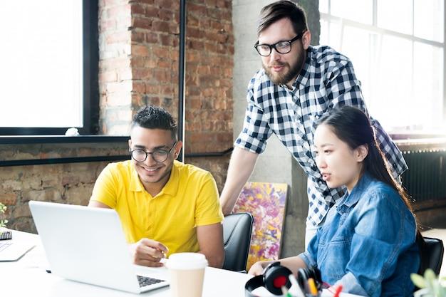 Creatief commercieel team dat computer in bureau met behulp van