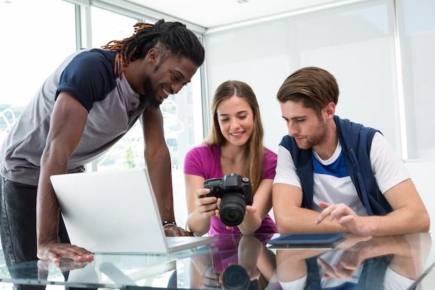 Creatief commercieel team dat digitale camera bekijkt
