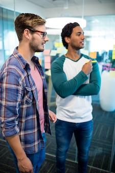Creatief commercieel team in bureau dat zich tegen de muur met plaknotities bevindt