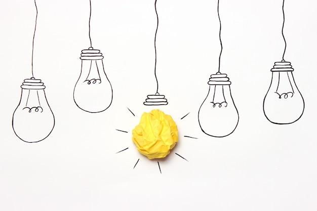 Creatief concept idee geschilderd gloeilamp met een verfrommeld papier gele bal