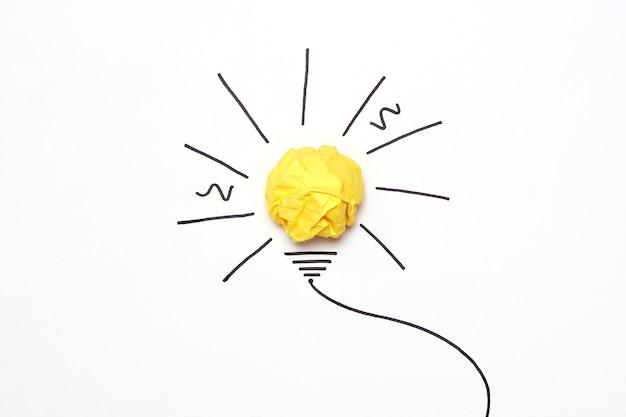Creatief concept idee geschilderde gloeilamp met een verfrommeld papier gele bal