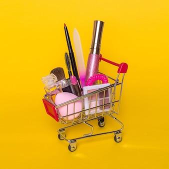 Creatief concept met winkelwagentje met make-up op een gele achtergrond.