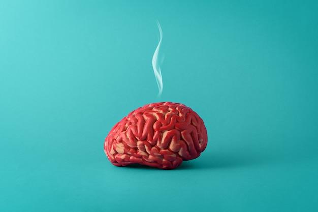 Creatief concept van een vermoeid brein op een blauwe achtergrond. menselijke hersenen met rook.
