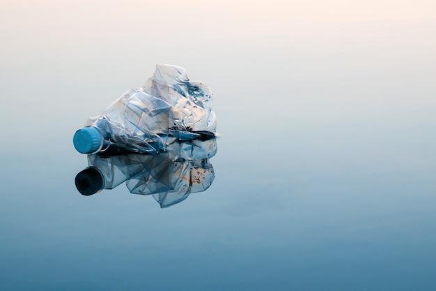 Creatief concept van verontreiniging. een plastic fles die in de oceaan drijft