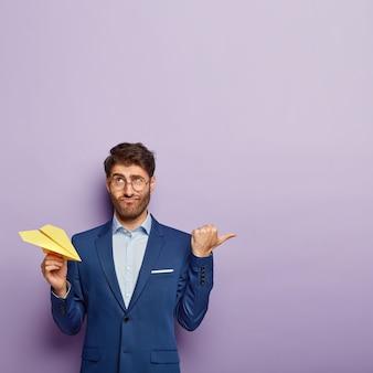 Creatief directeur houdt papier gemaakt geel vliegtuig vast, heeft een verbaasde blik