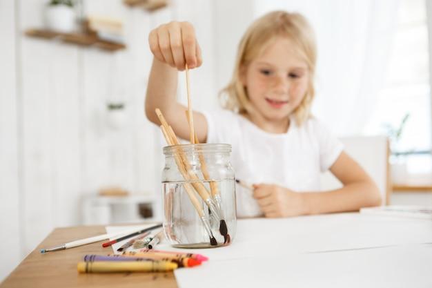 Creatief en blij blond meisje met sproeten die borstel in het water verdiepen. blonde vrouwelijk kind schilderen met een borstel. kunstactiviteiten voor kinderen.