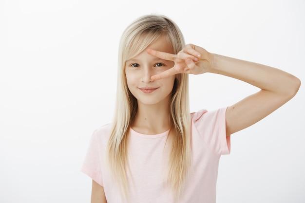 Creatief energiek kind wil disco dansen. portret van geïntrigeerd schattig blond meisje in roze t-shirt, overwinning of vredesteken boven oog tonen en breed glimlachend, met iets in gedachten