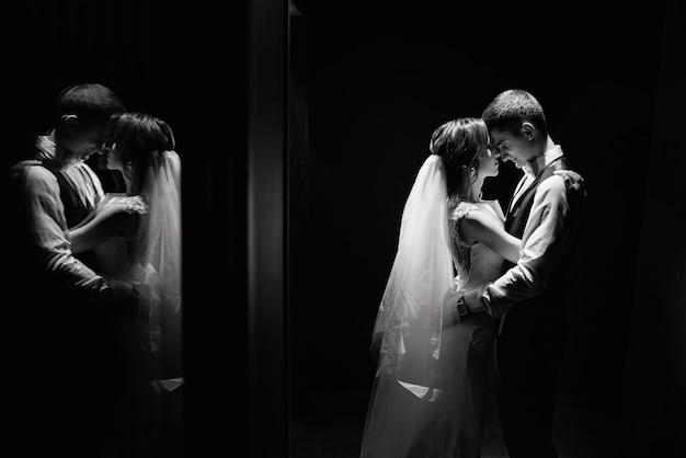 Creatief foto-idee van huwelijksfotografie in reflectie. bruid en bruidegom verlicht door lichten.