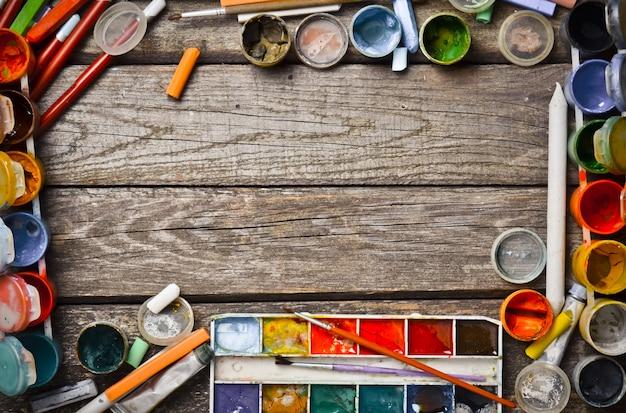 Creatief frame van producten voor tekenen en creëren. aquarellen, gouache, olieverf, kleurpotloden, kleurpotloden layout op een houten tafel. bovenaanzicht